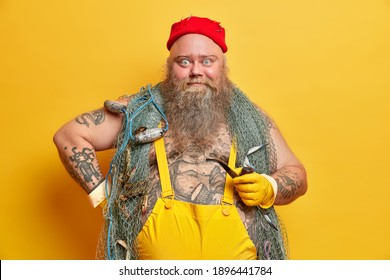 Surprised bearded man sailor wears red hat and overalls poses with fishing net holds smoking pipe keeps hand on waist poses against yellow studio background has tattooed body wondered expression