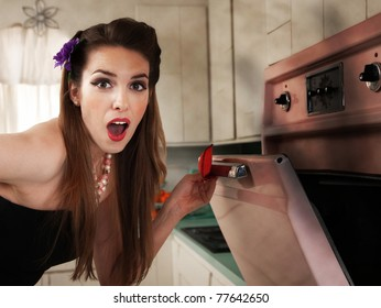 Surprised beautiful Caucasian housewife in kitchen checks her oven