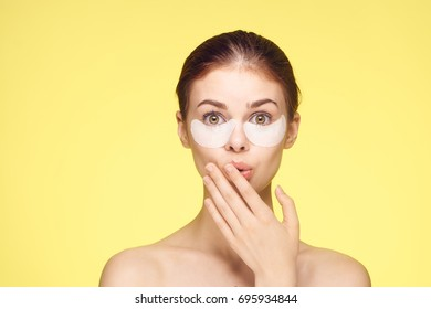 Surprised beautiful woman with patches under eyes, eye care on yellow background portrait