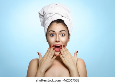 Surprised Beautiful Young Woman After Bath Touching Her Face With A Towel On Her Head Isolated On Blue Background. Skin Care And Spa Theme