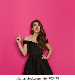 Surprised beautiful young woman in colorful vibrant striped mini dress is holding hands raised, presenting something, looking at camera and shouting. Studio shot on turquoise background.