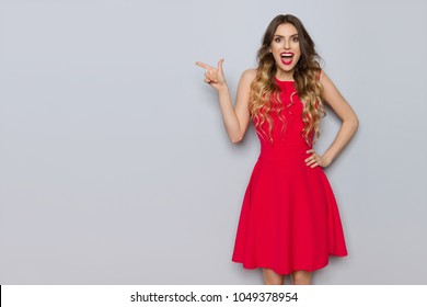Surprised beautiful young woman in red dress is pointing and shouting. Three quarter length studio shot on gray background.