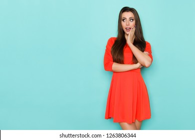 Surprised beautiful young woman in red mini dress is holding hand on chin and looking away. Three quarter length studio shot on blue background.