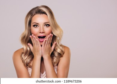 Surprised beautyful woman with opened mouth and blond hair. Woman in shock. Surprising facial emotions