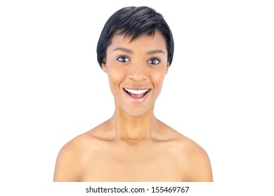 Surprised black haired woman smiling at camera on white background