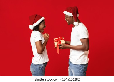 Surprised black lady looking at New Year gift in her beloved man hands, celebrating winter holidays together over red studio background, wearing Santa hats. Christmas, New Year celebration concept