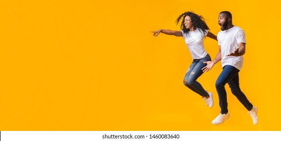 Surprised Black Man Is Looking At Free Space, afro woman is jumping and pointing at empty space, yellow background, panorama