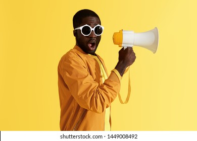 Surprised black man with megaphone on yellow background. Studio portrait of shocked african american male model in fashion sunglasses with loud speaker