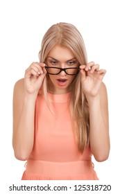 Überraschende blonde Frau, die über die Brille schaut