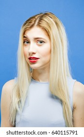 Surprised Blondel with Long Hair in Elegant Dress Posing on Blue Background in Studio and Looking at the Camera.