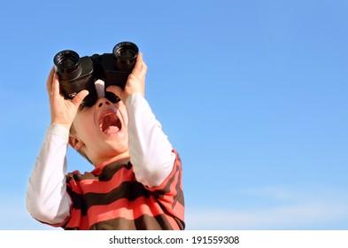 Surprised boy with binoculars against blue sky