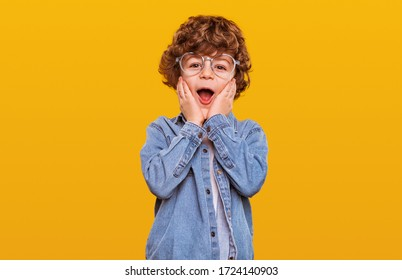 Surprised boy in denim jacket and glasses keeping hands near cheeks and looking at camera with opened mouth against yellow background