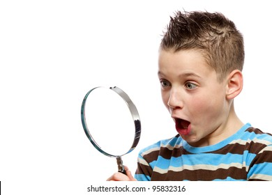 Surprised boy looking into a magnifier glass.