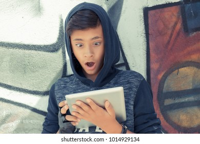 Surprised boy looking at the tablet pad isolated graffiti wall background