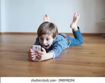 surprised boy lying on the wooden floor and using  mobile phone