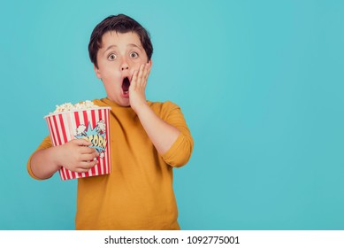 surprised boy with popcorn on blue background