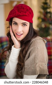 Surprised brunette on the couch at christmas at home in the living room
