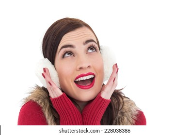 Surprised brunette in winter clothes on white background