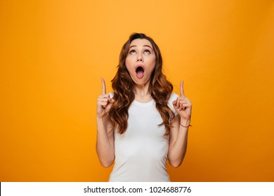 Surprised brunette woman in t-shirt pointing and looking up with open mouth over yellow background