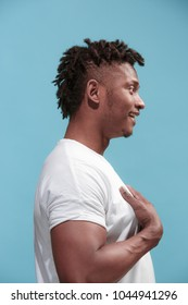 Surprised business Afro-American man standing and looking isolated on blue studio background. African American male profile portrait. Young emotional man. The human emotions, facial expression concept