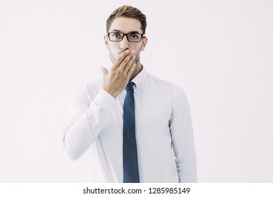 Surprised business man covering mouth with hand. Embarrassed attractive guy. Embarrassment concept. Isolated front view on white background.