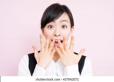 Surprised business woman against pink background