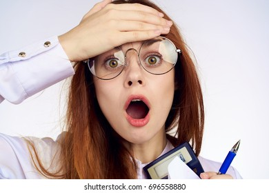 Surprised business woman with glasses holds a hand for her forehead in her hand calculator on a light background portrait