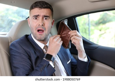 Surprised businessman with empty wallet after paying taxi