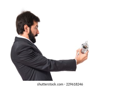 Surprised businessman holding a clock over white background