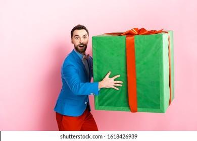 surprised businessman holding huge gift box on pink