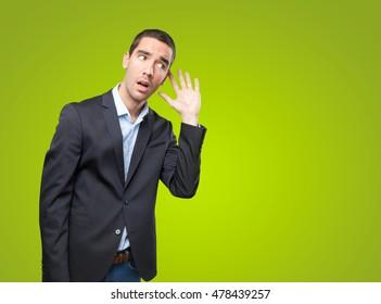 Surprised businessman listening on green background