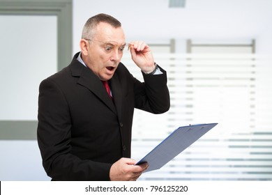 Surprised businessman reading a document in his office
