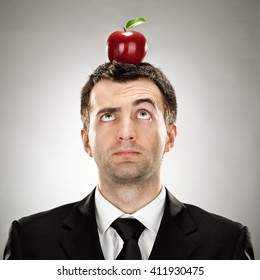 surprised businessman red apple on head on grey background
