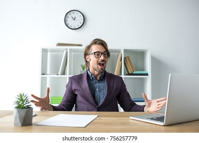 Surprised businessman shouting and looking at the laptop