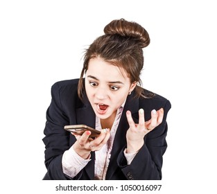 Surprised businesswoman girl looks into the phone, wearing a suit. Shock news. Isolated on white