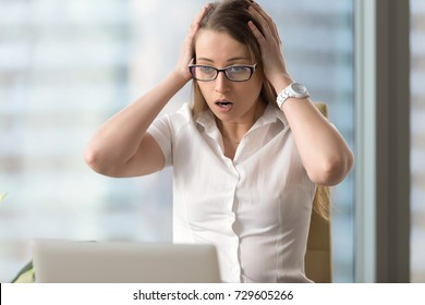 Surprised businesswoman looking at laptop pc, astonished woman with shocked face and open mouth holding head in hands, sudden unexpected computer crash, shocking news, fatal error, data loss, portrait