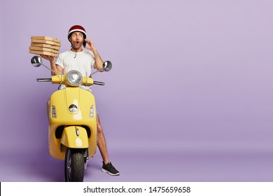 Surprised busy male delivers pizza, receives order from customer over smartphone, asks about address carries pile of cardboard containers, sits on motorbike, conveys food items isolated on purple wall