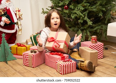 Ð¡hild is surprised by the gift for the new year against the background of the tree, sitting on the floor