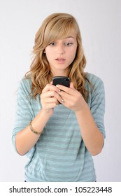 Surprised by Text Message. Thirteen year old girl reacting to a text message with shock and disbelief. Note: Not Isolated.