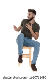 Surprised casual man apologizing while sitting on a chair on white studio background