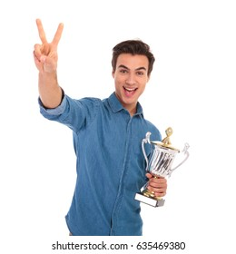 surprised casual man winning big troohy cup award and makes the victory or peace sign on white background