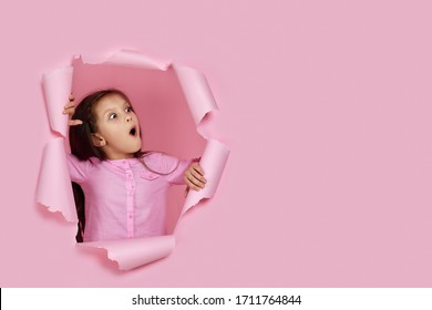 surprised caucasian little child girl looking with scared face expression aside in torn paper pink wall. banner for discounts and sales. copy space