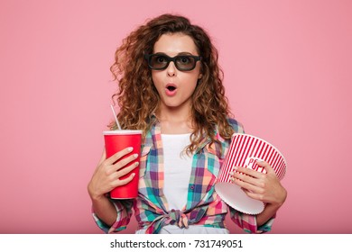 Surprised caucasian woman in 3d glasses holding cola and popcorn and looking camera isolated over pink