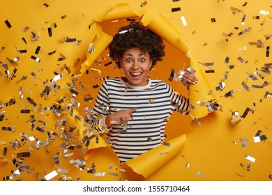 Surprised cheerful lady glad to be chosen, points at herself, smiles happily, dressed in casual striped wear, poses against vivid yellow backgroud in paper hole, says I am picked up. Best choice