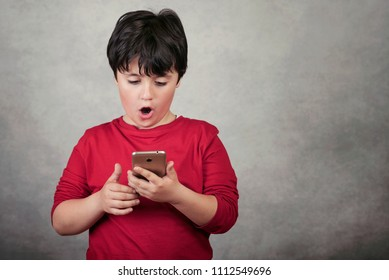 surprised child with a mobile phone on gray background