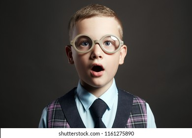 surprised child with an open mouth. kid in funny glasses. funny grimace little boy