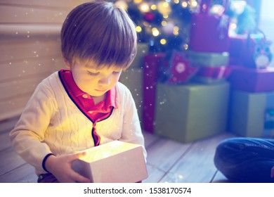 Surprised child opening and looking inside a magic gift over Christmas tree.