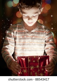 A surprised child opening and looking inside a magic gift
