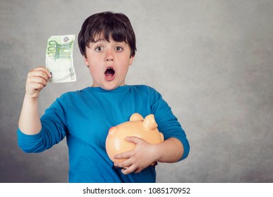 surprised child saving money in a piggy bank on gray background