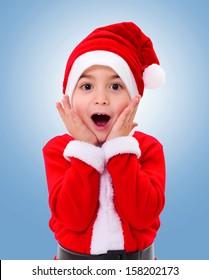 Surprised Christmas boy wearing blue Santa Claus uniform